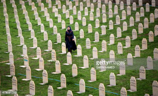 An Iraqi Kurd woman visits a grave yard for the victims of a gas attack by former Iraqi president Saddam Hussein in 1988, as people mark the 26th...