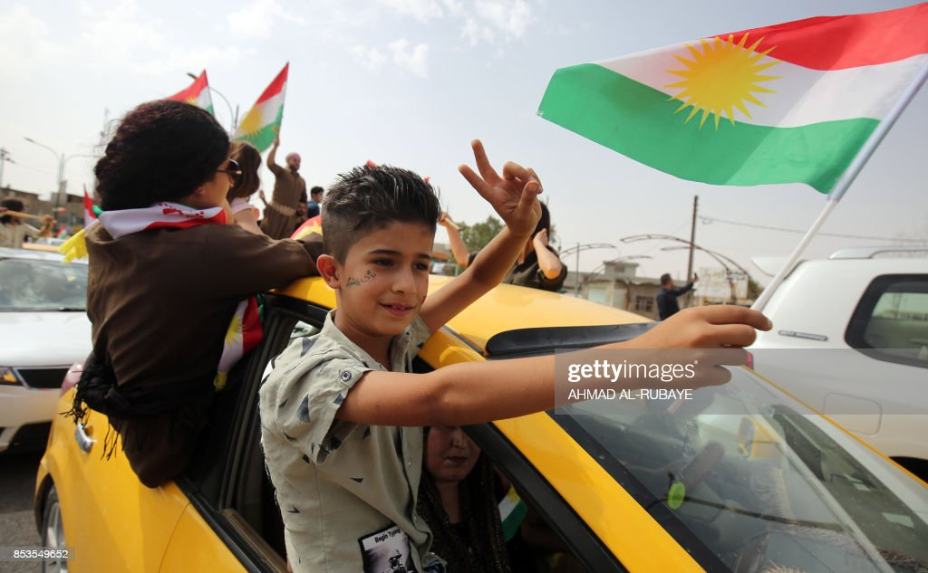 An Iraqi Kurdish boy waves a Kurdish flag as he rides outside a vehicle window while flashing the victory gesture, amid celebrations in the city of Kirkuk in northern Iraq, on September 25, 2017 as Iraqi Kurds vote in a referendum on independence. The non-binding vote, initiated by veteran Kurdish leader Massud Barzani, has angered not only Baghdad, following which Iraq's federal parliament demanded that troops be sent to disputed areas in the north controlled by the Kurds since 2003, but also neighbours Turkey and Iran who are concerned it could stoke separatist aspirations among their own sizeable Kurdish minorities. /