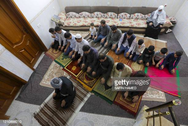 An Iraqi Kurdish family prays in their home on the first day if the Muslim holy month of Ramadan on April 24 in Arbil the capital of the northern...