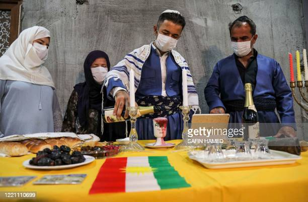 An Iraqi Kurdish Jewish man clad in mask due to the COVID19 coronavirus pandemic and a Tallit prayer shawl pours wine into a cup near a Kurdish flag...