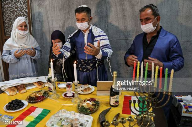 An Iraqi Kurdish Jewish man clad in mask due to the COVID19 coronavirus pandemic and a Tallit prayer shawl and other family members recite a prayer...