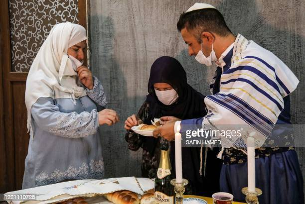 An Iraqi Kurdish Jewish man clad in mask due to the COVID19 coronavirus pandemic and a Tallit prayer shawl breaks a loaf of bread with family members...
