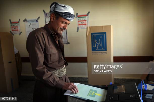 TOPSHOT An Iraqi Kurdish man dressed in traditional costume puts his ballot through an electronic counting machine into a ballot box at poll station...