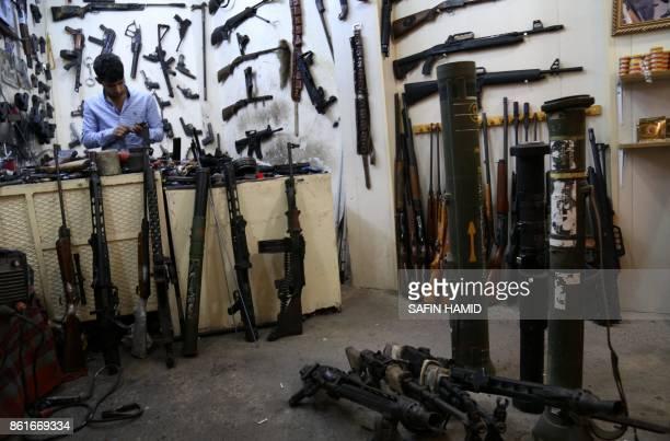 An Iraqi Kurdish man inspects a handgun at his firearmrepair workshop in Arbil the capital of the autonomous Kurdish region of northern Iraq on...