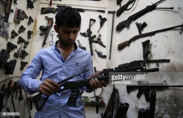 An Iraqi Kurdish man inspects an assault rifle at his firearmrepair workshop in Arbil the capital of the autonomous Kurdish region of northern Iraq...