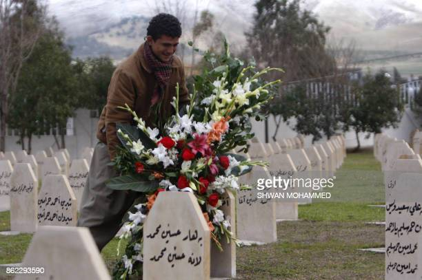 An Iraqi Kurdish man lays flowers on the grave of a relative killed in the Halabja attacks in 1988 in the northern town of Halabja on January 26,...