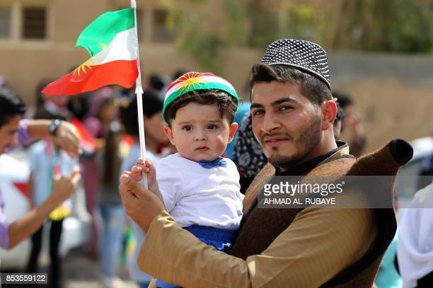 An Iraqi Kurdish man poses as he carries a child wearing the Kurdish flag on his head during a celebration in the northern city of Kirkuk on...