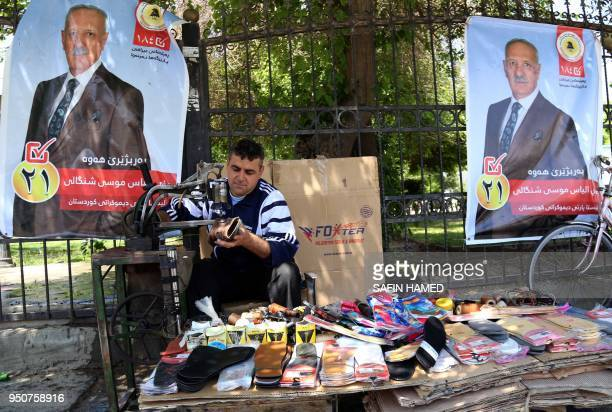 An Iraqi Kurdish man repairs shoes in front of an election campaign poster in Arbil the capital of the northern Iraqi Kurdish autonomous region on...