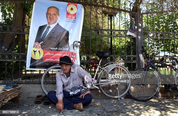 An Iraqi Kurdish man sits in front of an election campaign poster in Arbil the capital of the northern Iraqi Kurdish autonomous region on April 24...