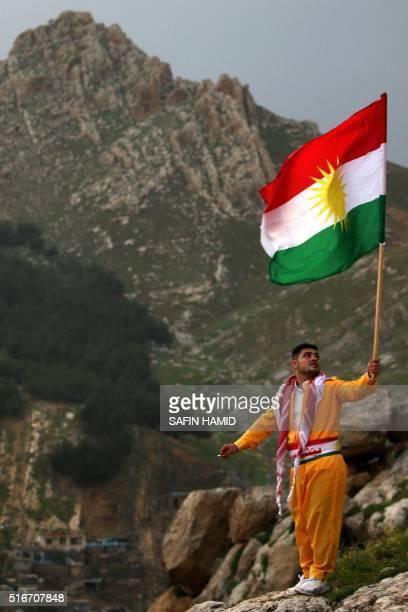 An Iraqi Kurdish man stands holding the Kurdish flag as he celebrates Noruz the Persian new year in the Kurdish town of Aqrah 500 kiloemtres north of...