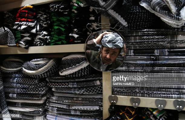 An Iraqi Kurdish man tries a traditional outfit during the annual celebrations of Noruz the Persian New Year on March 19 in Arbil the capital of the...