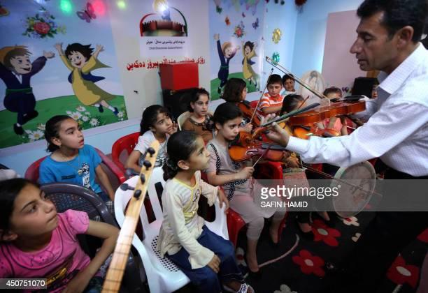 An Iraqi Kurdish music teacher gives a music lesson at a summer school in Arbil the capital of the autonomous Kurdish region of northern Iraq on June...