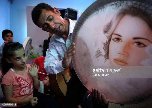 An Iraqi Kurdish music teacher instructs a girl during a music lesson at a summer school in Arbil the capital of the autonomous Kurdish region of...
