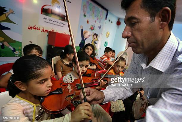 An Iraqi Kurdish music teacher instructs a girl on how to play the violin during a music lesson at a summer school in Arbil the capital of the...