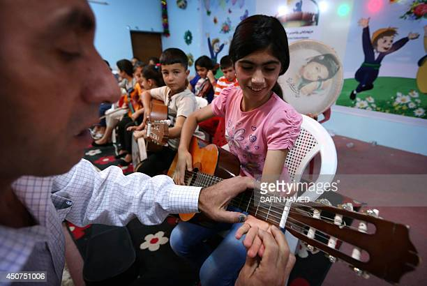 An Iraqi Kurdish music teacher instructs a girl on using a spanish guitar during a music lesson at a summer school in Arbil the capital of the...