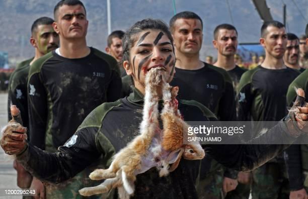 An Iraqi Kurdish Peshmerga female officer bites a Rabbit while demonstrating skills during a graduation ceremony in the Kurdish town of Soran about...