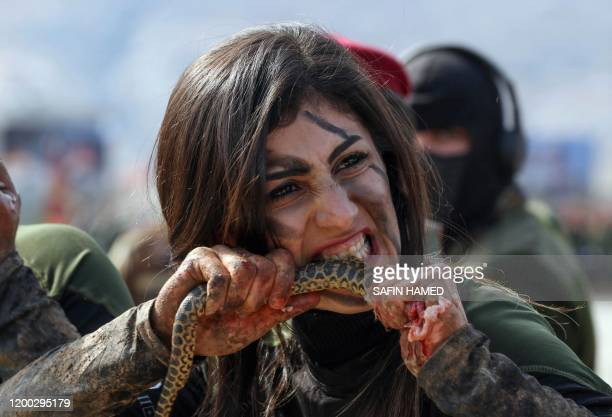 An Iraqi Kurdish Peshmerga female officer bites a snake while demonstrating skills during a graduation ceremony in the Kurdish town of Soran, about...