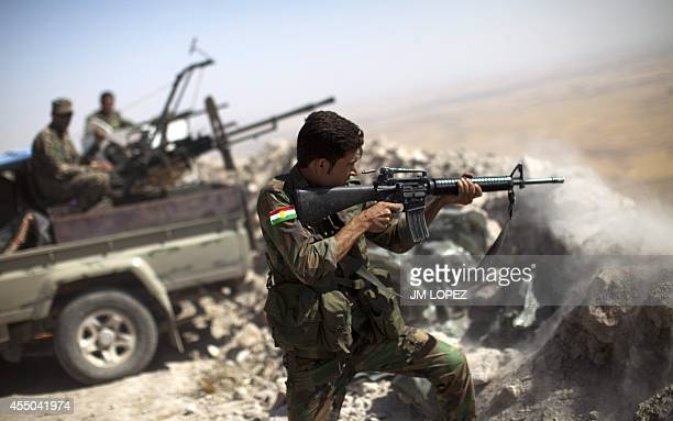 An Iraqi Kurdish Peshmerga fighter fires at IslamicState militant positions from his position on the top of Mount Zardak a strategic point taken 3...