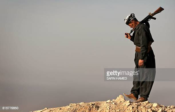 An Iraqi Kurdish Peshmerga fighter holds a position in Sheikh Ali village near the town of Bashiqa, some 25 kilometres north east of Mosul, on...
