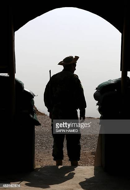 An Iraqi Kurdish Peshmerga fighter holds position during a visit of archbishop Yohanna Boutros Moshe of Mosul to the top of Mount Zardak about 25...