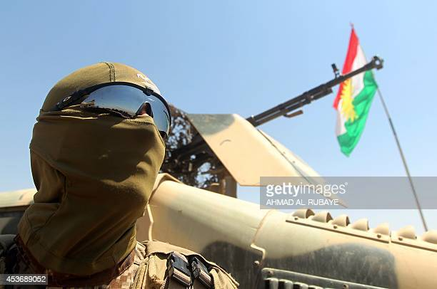 An Iraqi Kurdish Peshmerga fighter monitors the area from their front line position in Bashiqa a town 13 kilometres northeast of Mosul on August 16...