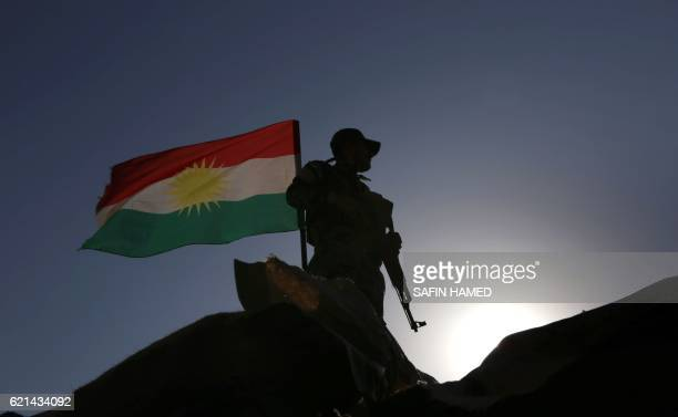 TOPSHOT An Iraqi Kurdish Peshmerga fighter next to a Kurdish flag holds a position in Sheikh Ali village near the town of Bashiqa some 25 kilometres...