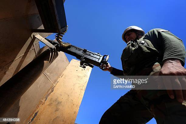 An Iraqi Kurdish Peshmerga fighter stands behind an armourplate shield holding a machine gun as he guards a position at the frontline of fighting...