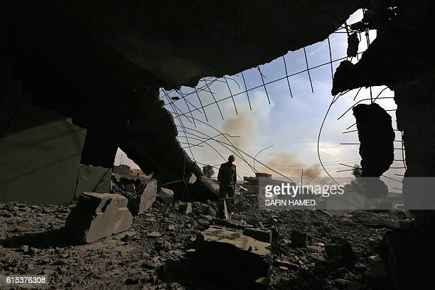 An Iraqi Kurdish Peshmerga fighter stands inside of a building on October 18 2016 on the frontline in the Shaqouli village about 35 kms east of Mosul...