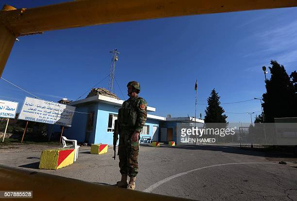 An Iraqi Kurdish Peshmerga stands guard at the entrance of the Mosul Dam on the Tigris River around 50 kilometres north of the city of Mosul on...