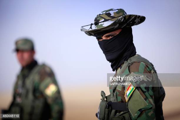 An Iraqi Kurdish security guard stands guard as Iraqi families fleeing violence in the northern Nineveh province gather at a Kurdish checkpoint in...