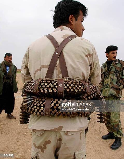 An Iraqi Kurdish soldier stands at the last checkpoint along a road to Kirkuk city as he carries hundreds of bullets in a bandolier March 7, 2003 in...