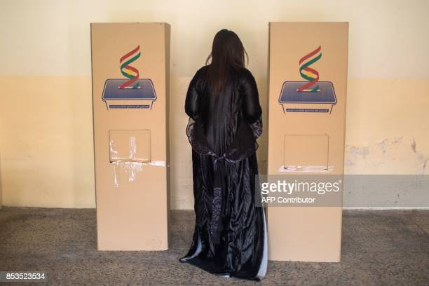 An Iraqi Kurdish woman casts her vote in the Kurdish independence referendum at a school in Arbil which is being used as a polling station on...