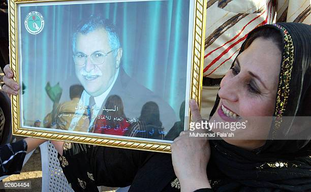 An Iraqi Kurdish woman holds a picture of veteran Kurdish leader Jalal Talabani during celebration of his inauguration April 8 2005 in Baghdad Iraq...