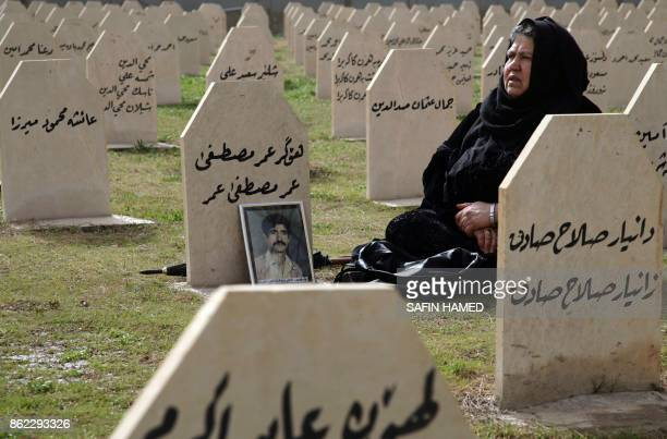An Iraqi Kurdish woman visits the grave of her relative Omar Mustafa who was killed in a gas attack by former Iraqi president Saddam Hussein in 1988...