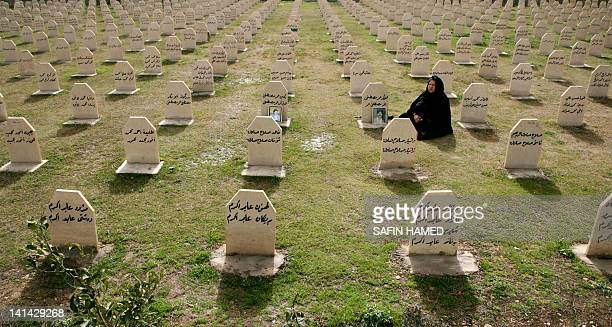 An Iraqi Kurdish woman visits the grave of her relatives Hafkar Omar Mustafa and Neghin Mustafa who were killed in a gas attack by former Iraqi...