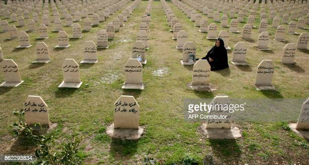 An Iraqi Kurdish woman visits the grave of her relatives, Hafkar Omar Mustafa and Neghin Mustafa who were killed in a gas attack by former Iraqi...