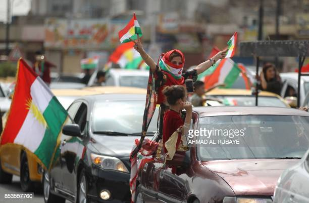An Iraqi Kurdish woman wearing the Kurdish flag on her face flashes the victory gesture amid celebrations in the city of Kirkuk in northern Iraq on...