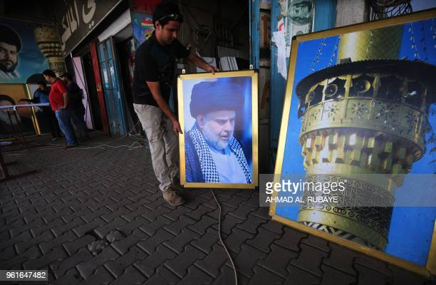 TOPSHOT An Iraqi labourer works on a poster of Shiite cleric Moqtada Sadr at a printing shop in Sadr City east of the Iraqi capital Baghdad on May 23...