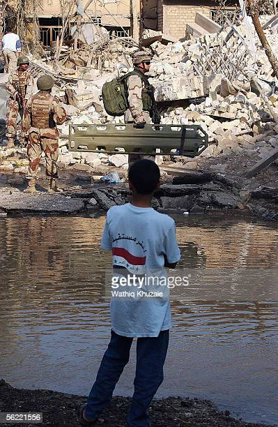 An Iraqi local boy looks at an American soldier securing the site where two suicide car bombs exploded near an Interior Ministry building causing...