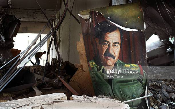 An Iraqi looks for items to loot behind a portrait of Saddam Hussein in a bombed government building April 8 2003 in Basra Iraq Coalition forces...