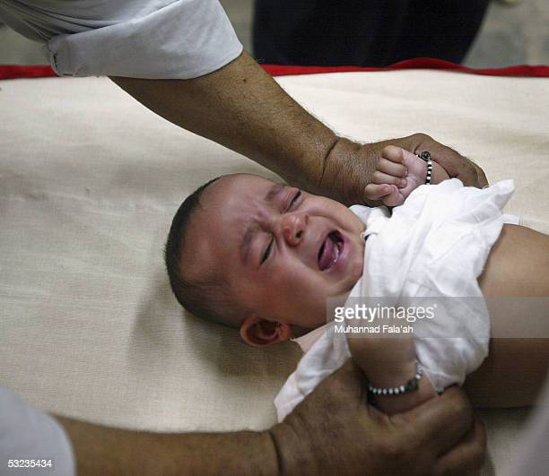 An Iraqi male child cries as he is circumcised July 14 2005 in Baghdad Iraq Circumcision is a religious practice among Muslims and is seen as an act...