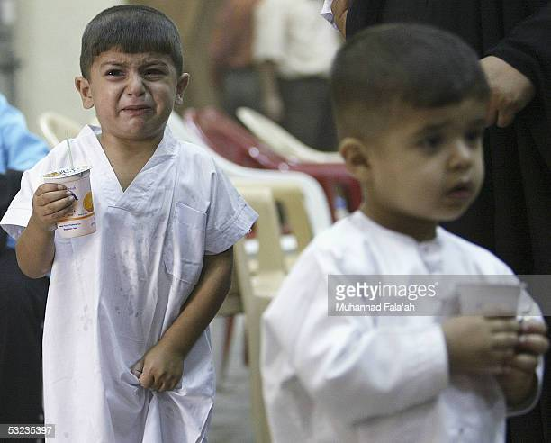 An Iraqi male child cries as he stands in line to be circumcised July 14 2005 in Baghdad Iraq Circumcision is a religious practice among Muslims and...