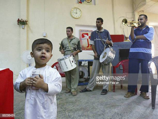 An Iraqi male child waits to be circumcised as a musical band play July 14, 2005 in Baghdad, Iraq. Circumcision is a religious practice among Muslims...