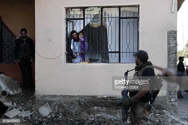 TOPSHOT An Iraqi man and his daughter gesture to soldiers from the Iraqi Special Forces patrolling a street in the Aden district of Mosul after...