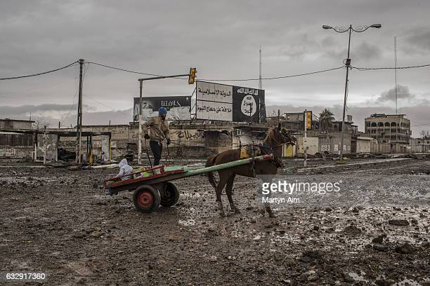 An Iraqi man and his son on a horse and cart pass an Islamic State billboard in Nebi Yunus on January 28 Eastern Mosul Iraq The liberation of eastern...