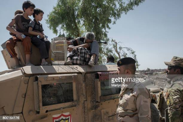 An Iraqi man and his sons sit on top of an Iraqi Army humvee after fleeing the Islamic State controlled Old City of west Mosul where heavy fighting...