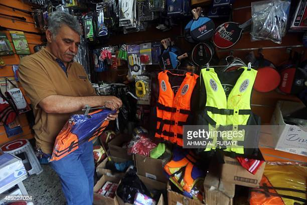 DUNLOP An Iraqi man arranges life jackets at his shop on Rashid Street where many of the Baghdad's sports shops are located on September 13 as demand...