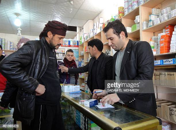 An Iraqi man buys medicine at a pharmacy in the center of the city of Fallujah, west of the capital Baghdad on January 8 following days of fighting...