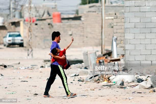 An Iraqi man carries a boy as he walks along a street in alZubair south of Basra on February 11 2018 Informal housing settlements are flourishing in...