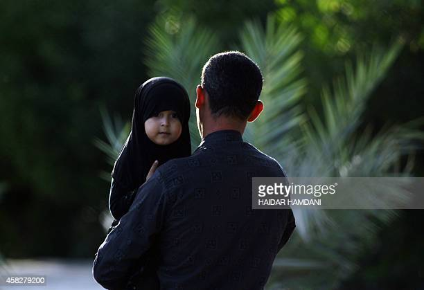 An Iraqi man carries a child on on the eve of the peak of the mourning period of Ashura in the northern Iraqi holy city of Najaf on November 2 2014...